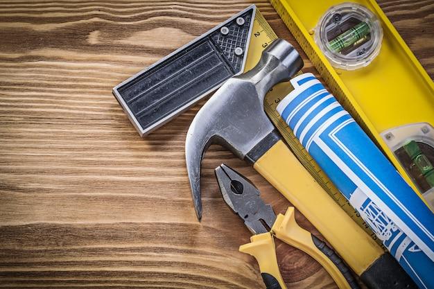 Il livello di costruzione delle cianografie blu prova le pinze quadrate del martello da carpentiere sulla tavola di legno