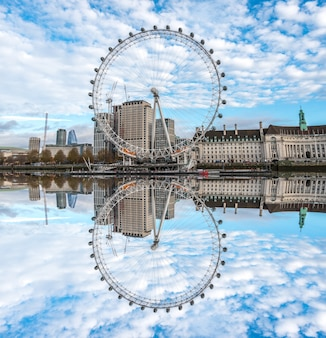 Il london eye si riflette sul tamigi a londra