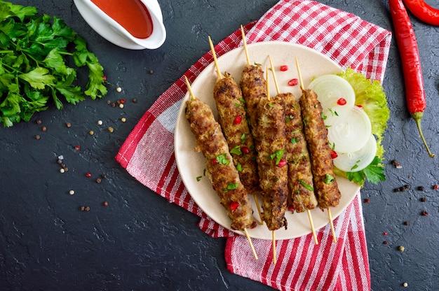 Il lula kebab è un piatto arabo tradizionale. shashlik di carne su spiedini di legno su sfondo nero. la vista dall'alto