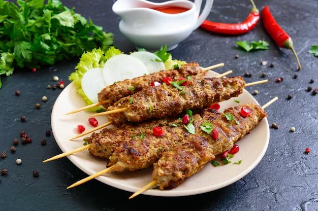 Il lula kebab è un piatto arabo tradizionale. shashlik di carne su spiedini di legno su sfondo nero.
