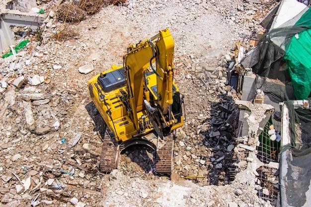 Il macchinario dell'escavatore a cucchiaia rovescia che lavora alla demolizione del sito di un vecchio edificio.