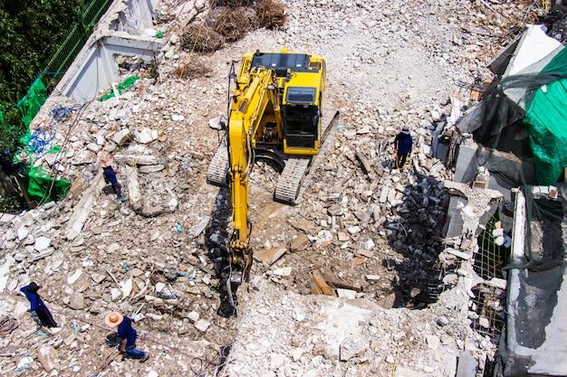 Il macchinario dell'escavatore a cucchiaia rovescia che lavora alla demolizione del sito di vecchi lavoratori edili.