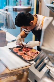 Il macellaio asiatico sta organizzando fette rare di alta qualità in molte parti del wagyu
