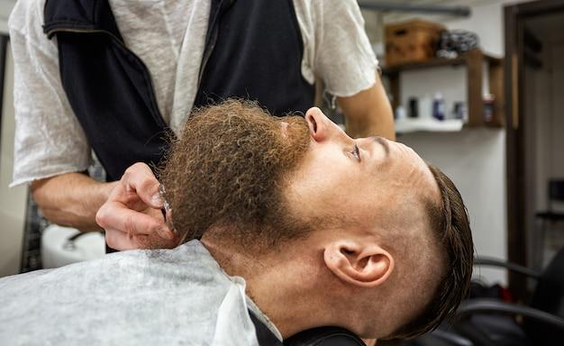 Il maestro barbiere fa acconciatura e styling. concept barbershop. taglio e taglio della barba. styling della barba nera. così alla moda ed elegante. concetto di pubblicità e negozio di barbiere