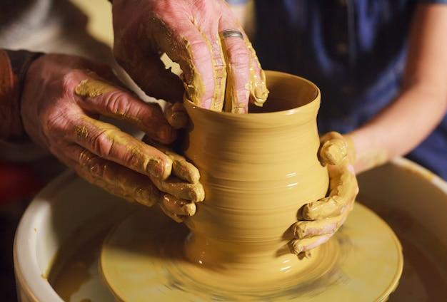 Il maestro con il bambino modella una brocca di argilla.
