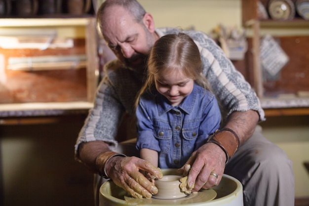 Il maestro con il bambino modella una brocca di terracotta.