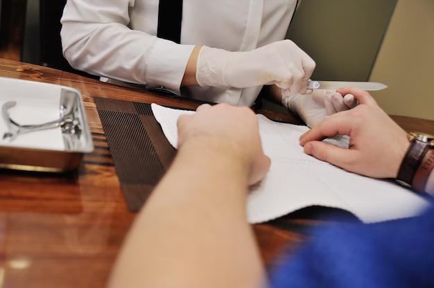 Il maestro del salone di bellezza fa una manicure per un cliente maschio