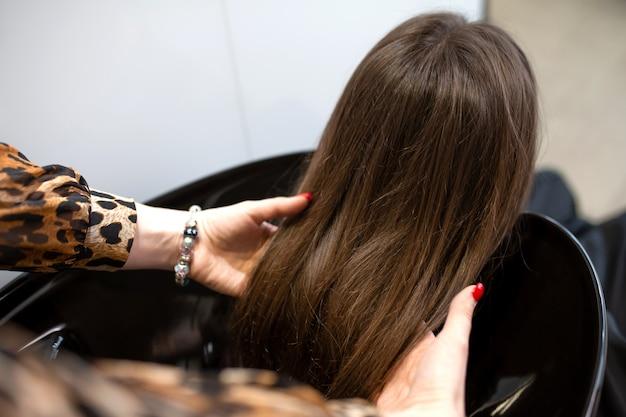 Il maestro del taglio di capelli lava i capelli di quelli del suo cliente