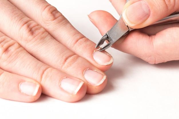 Il maestro della manicure taglia la cuticola dalle dita del cliente nel salone di bellezza