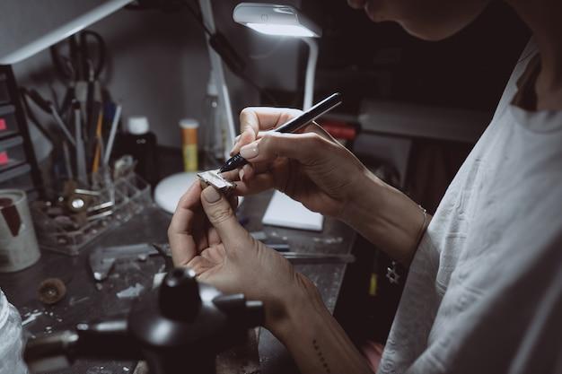 Il maestro elabora il metallo prezioso nell'officina domestica