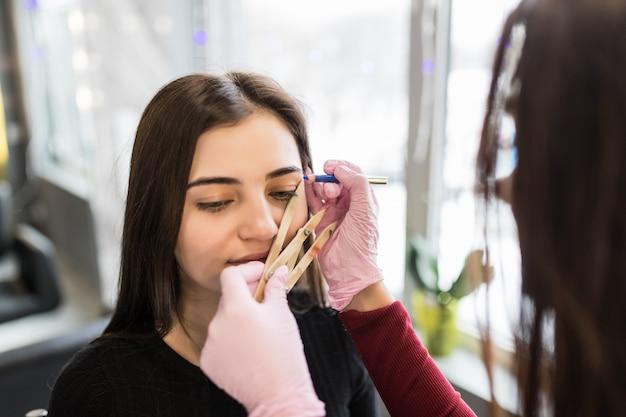 Il maestro in guanti bianchi lavora alla tecnica delle sopracciglia posteriori nel salone di bellezza