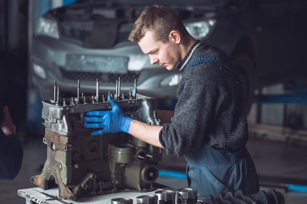 Il maestro raccoglie un motore ricostruito per l'auto.