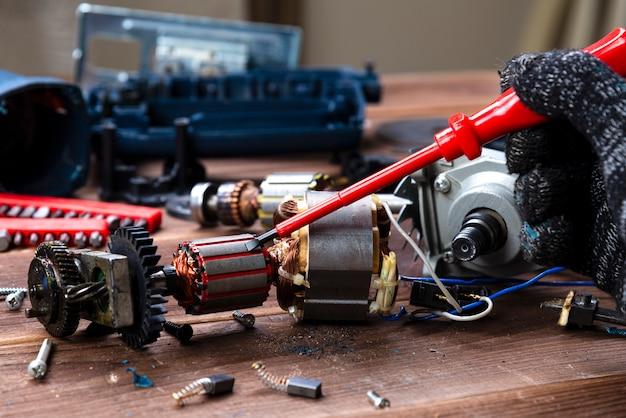 Il maestro ripara un dispositivo elettrico rotto: trapano, taglierina su un tavolo di legno. officina riparazioni utensili elettrici