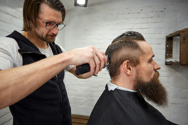 Il maestro taglia i capelli e la barba degli uomini nel barbiere, il parrucchiere fa acconciatura per un giovane
