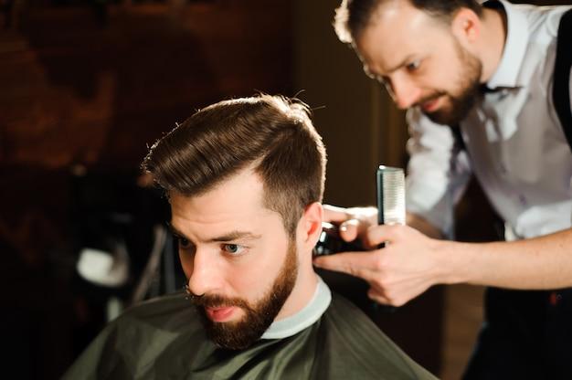 Il maestro taglia i capelli e la barba degli uomini nel barbiere