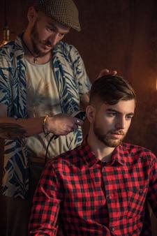 Il maestro taglia i capelli e la barba degli uomini