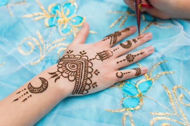 Il maestro tatuatore mehndi disegna sulla mano della donna