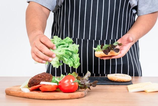 Il maggiordomo sta cucinando un hamburger che contiene verdure fresche, carne e sheese
