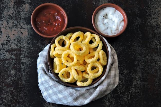 Il mais suona in una ciotola con salsa rossa e bianca. flat lay.