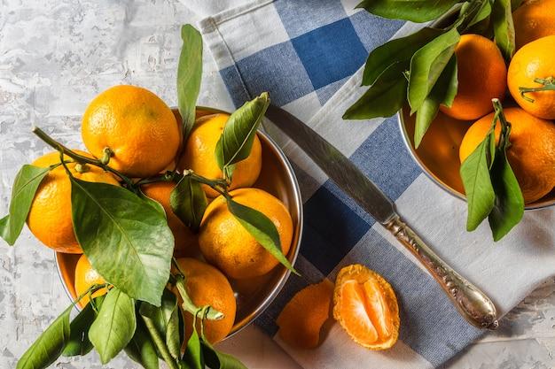Il mandarino maturo arancio fruttifica con le foglie verdi in ciotole, sopra fondo di legno bianco rustico.
