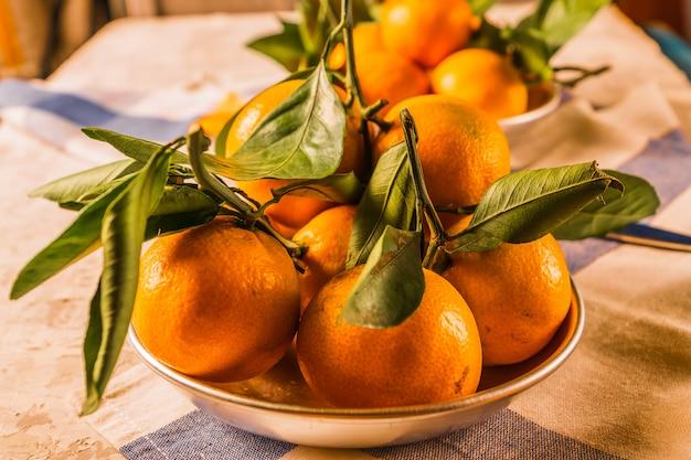 Il mandarino maturo arancio fruttifica con le foglie verdi in una ciotola, sopra fondo di legno bianco rustico.