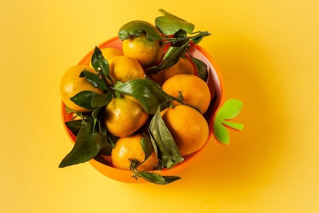 Il mandarino maturo arancio fruttifica con le foglie verdi in una ciotola, sopra fondo giallo.