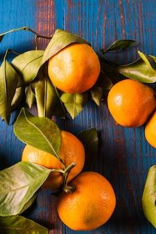 Il mandarino maturo arancio fruttifica con le foglie verdi sopra fondo di legno blu rustico.