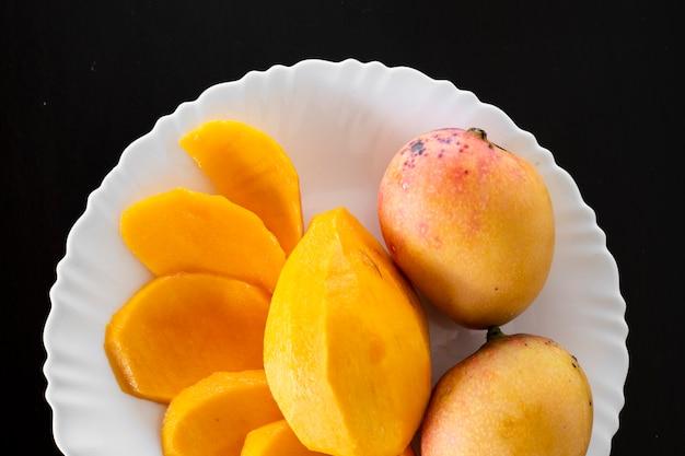 Il mango è un frutto di varia colorazione, originario del sud e del sud-est asiatico. foto di mango con un piatto bianco e un bicchiere con succo di mango.