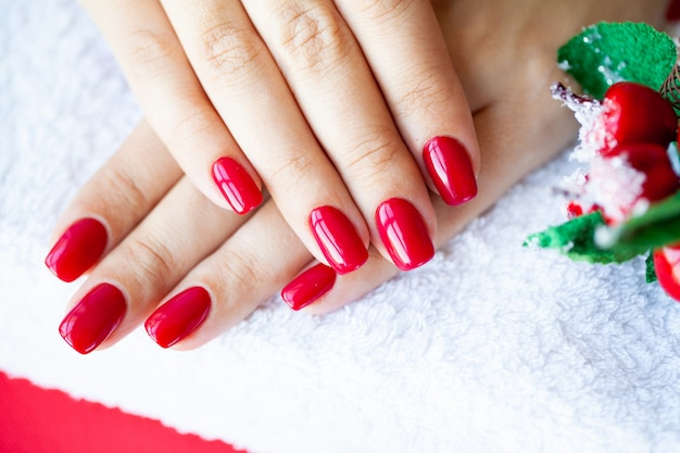 Il manicure rosso di natale fa nello studio di bellezza