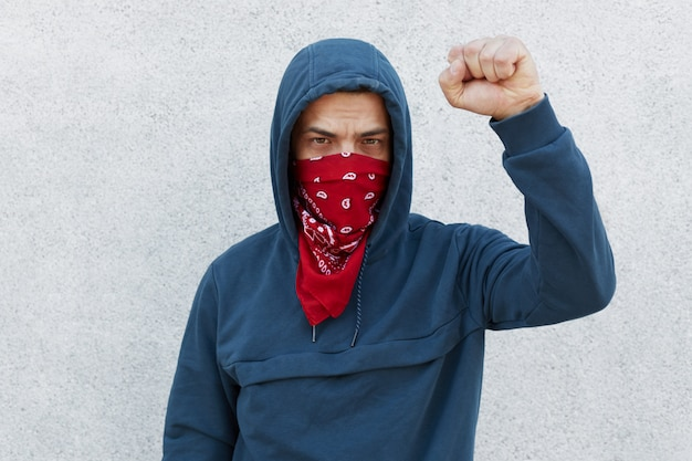 Il manifestante con la maschera di bandana rossa alza il pugno