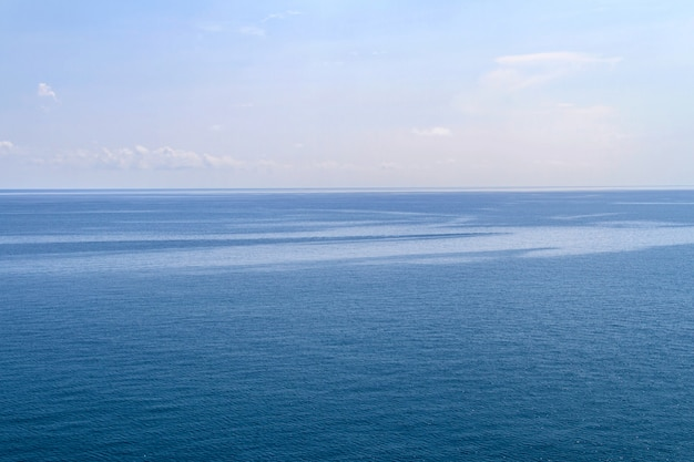 Il mare e la barca a vela blu con le nuvole annebbiano il cielo