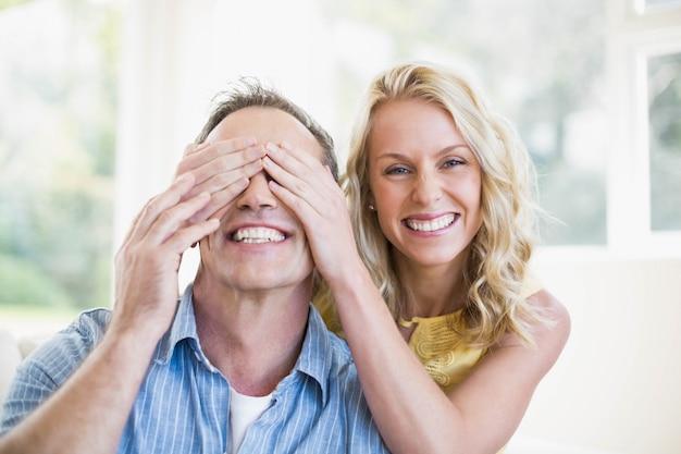 Il marito della copertura della moglie felice osserva nel salone