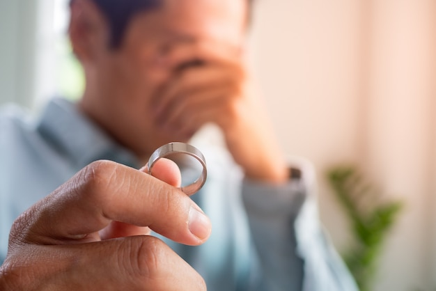 Il marito piange tristemente tenendo in mano un anello nuziale dopo una discussione con sua moglie e decide di separarsi