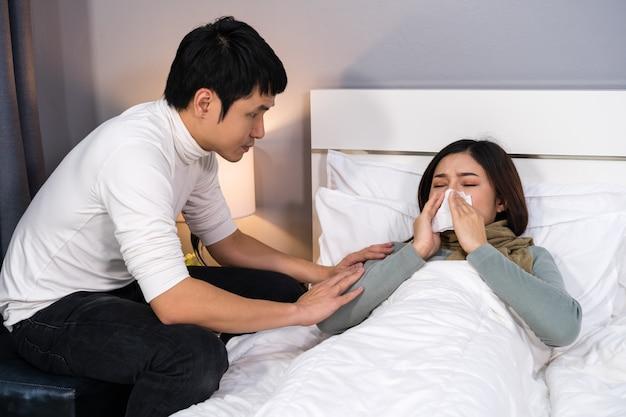Il marito visita e si prende cura della moglie malata mentre è sdraiata sul letto a casa