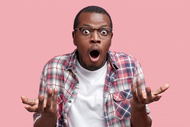 Il maschio afroamericano frustrato si sente perplesso ed esitante, alza le spalle perplesso, tiene la bocca ben aperta, non sa cosa fare