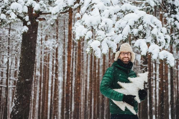 Il maschio barbuto bello indossa un berretto di pelliccia caldo con paraorecchie e giacca a vento verde