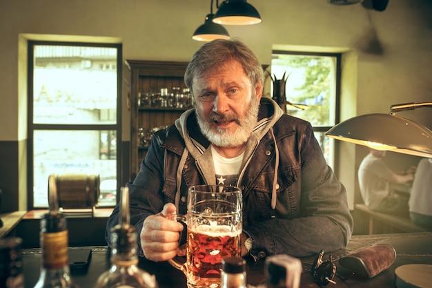 Il maschio barbuto senior che beve birra in pub