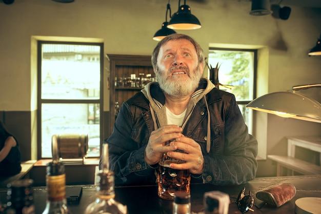 Il maschio barbuto senior triste che beve birra in pub