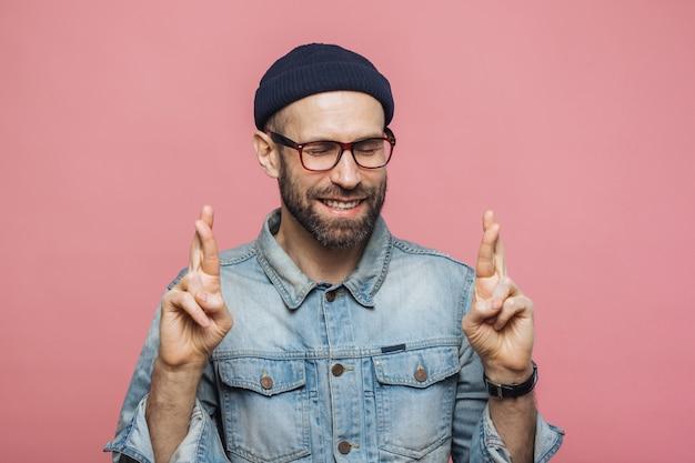Il maschio con la barba lunga positivo con lo sguardo felice incrocia le dita, tiene gli occhi chiusi, ha un grande desiderio e speranza per il meglio
