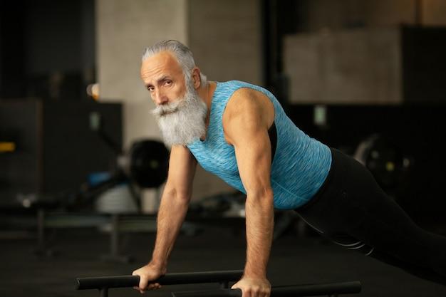 Il maschio maggiore barbuto serio sta godendo dello stile di vita sportivo