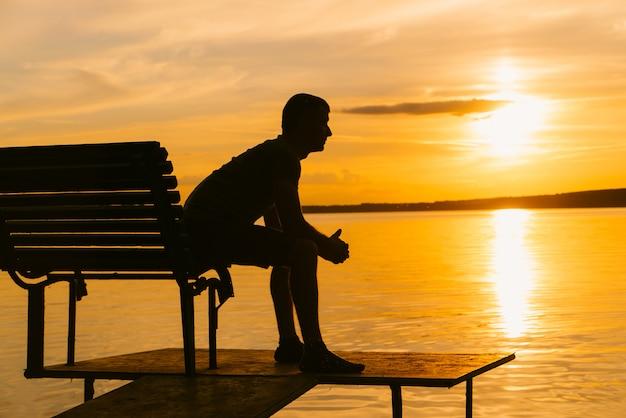 Il maschio si siede sul bordo del banco di legno sulla passerella nel fiume al tramonto