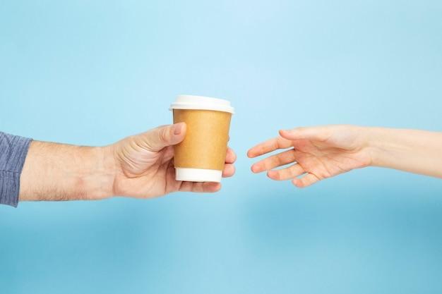 Il maschio tiene la tazza di carta della mano con la femmina del caffè prende la tazza su fondo blu