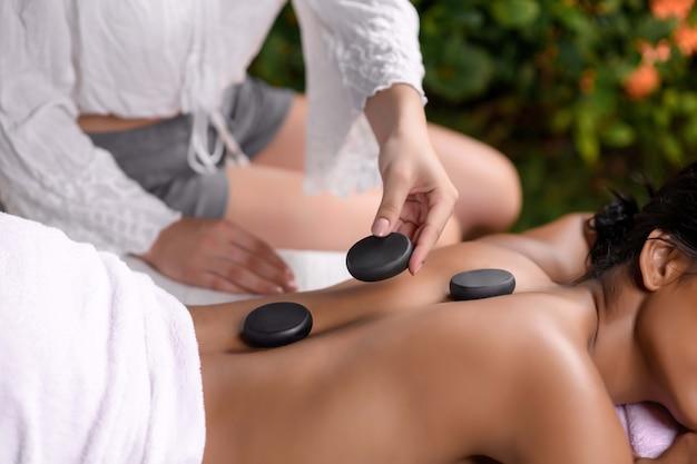 Il massaggiatore pone le pietre per la terapia della pietra sulla schiena di una giovane ragazza