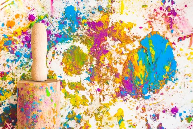 Il mattarello vicino a sfocature e cumuli di diversi colori brillanti e secchi