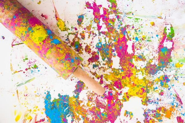 Il mattarello vicino alle sfocature di diversi colori secchi e brillanti