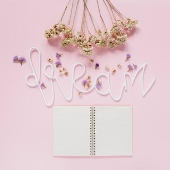 Il mazzo dei fiori bianchi e la lavanda fiorisce sul testo di sogno con un diario aperto sopra il contesto rosa