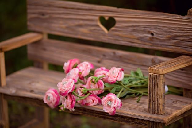 Il mazzo del ranunculus fiorisce su un vecchio banco di legno sulla natura dell'estate