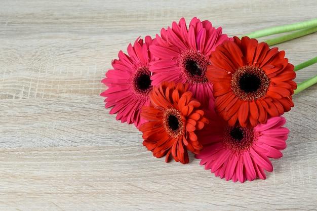 Il mazzo della gerbera fiorisce sul primo piano grigio di legno del fondo. bel regalo per festeggiare qualsiasi vacanza.