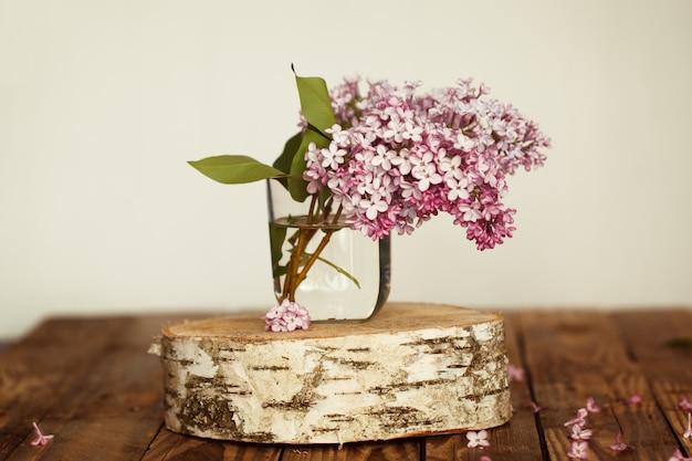 Il mazzo della molla lilla fiorisce su fondo di legno.
