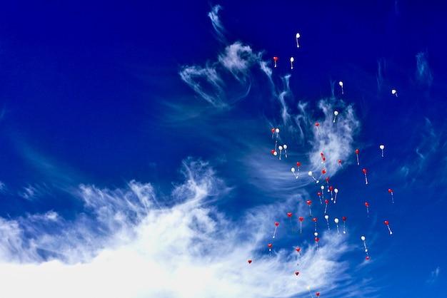 Il mazzo di impulsi rossi e bianchi ha rilasciato e salendo al cielo blu nuvoloso durante la celebrazione